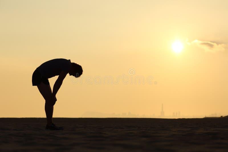 一位被用尽的运动员的剪影日落的 库存照片