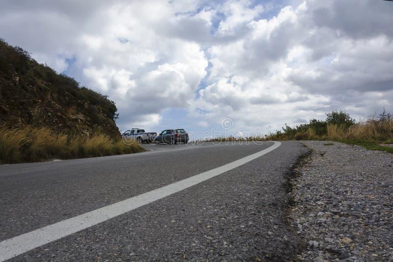 一位警察和一辆民用汽车在山路 免版税图库摄影