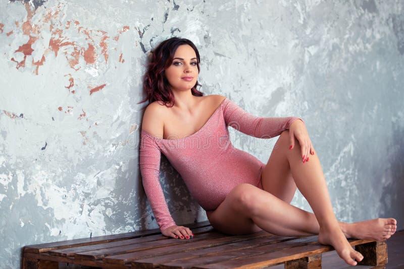 一位身穿时尚粉色紧身衣、身着棕色板条的灰色墙壁的美女怀孕 免版税库存照片