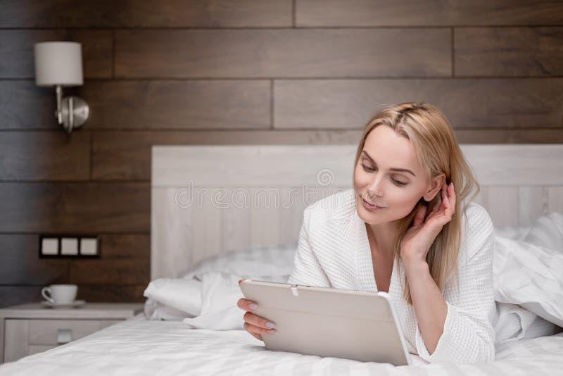 一位身穿白色浴袍的漂亮中年金发女子躺在卧室的床上,用的是平板电脑 免版税库存图片