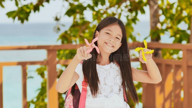一位转动锭床工人的小菲律宾女小学生展示 热带的横向 夏天 童年 免版税库存图片