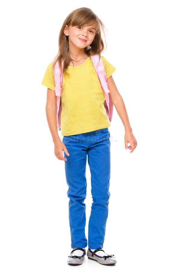一位逗人喜爱的矮小的女小学生的画象有背包的 库存照片