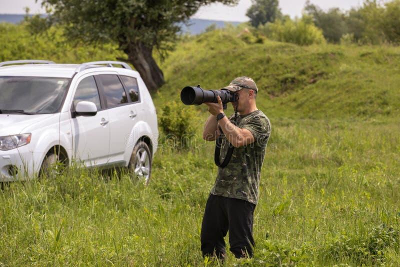 一位野鸟观察者和鸟摄影师有一个大远摄镜头的 免版税图库摄影
