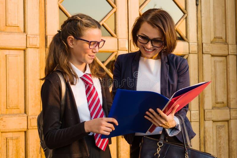 一位高中老师与一个女学生谈话在fr附近 免版税库存图片