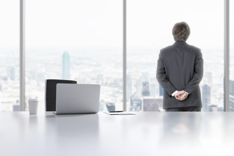 一位年轻专家在现代全景办公室看窗口在曼哈顿,纽约 膝上型计算机、笔记薄和a 库存照片