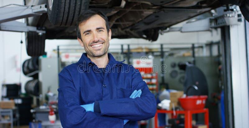 一位年轻美丽的汽车修理师的画象在一个汽车车间,在服务背景中  概念:机器修理,缺点dia 免版税库存照片