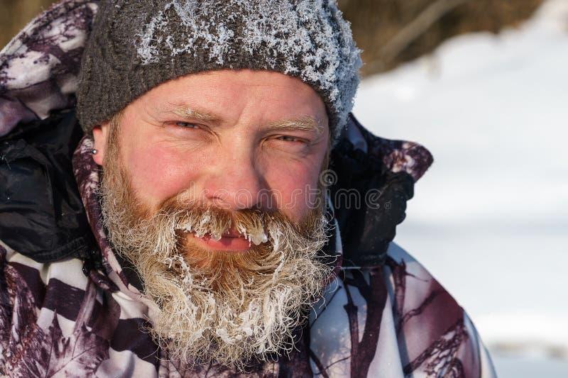 一位euriopean有胡子的渔夫人或猎人与冰和树冰在胡子看对照相机与微笑 免版税库存图片