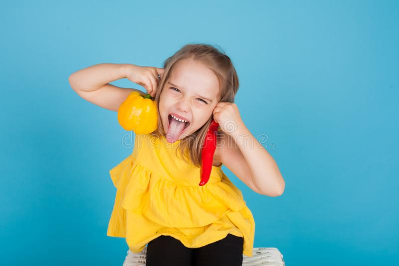 一俏丽的女孩的画象有黄色的新鲜蔬菜和红辣椒的 库存照片