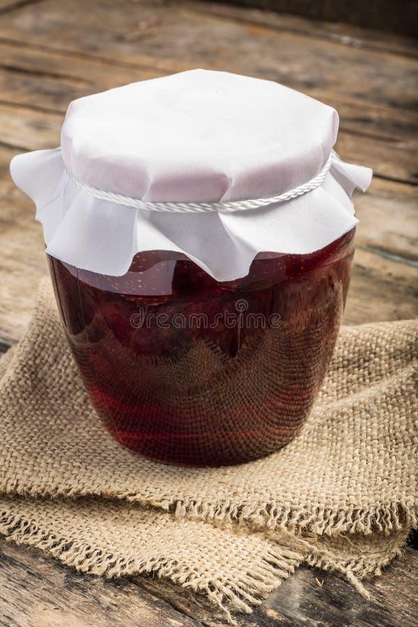 一关闭了瓶子在木背景的草莓酱 免版税图库摄影