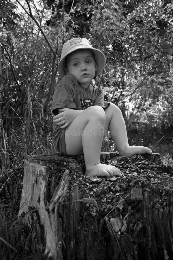 一冻女孩赤足坐树桩 黑白图象 免版税库存照片