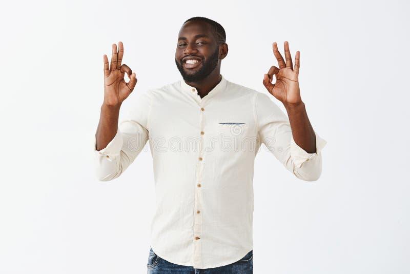 一切是优秀的 在显示白色的衬衣的满意的可爱的非裔美国人的男性商人好或好 免版税库存图片