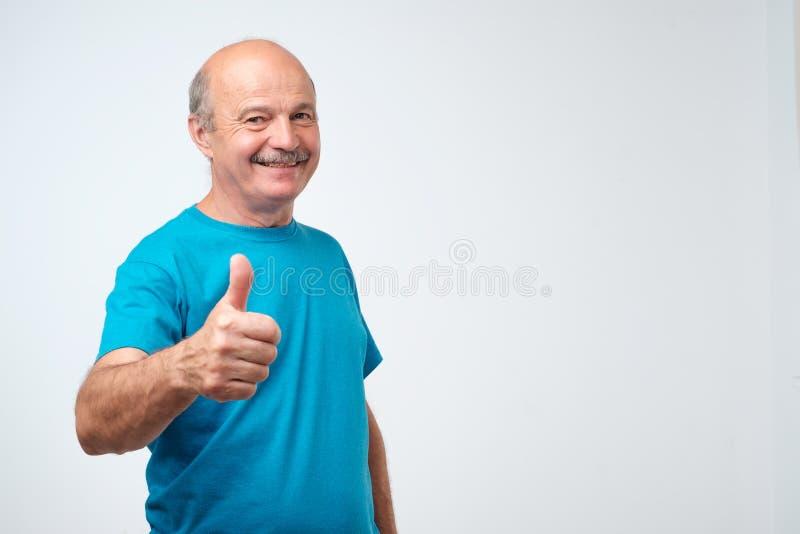 一切是伟大的 蓝色T恤杉的正面好成熟快乐的人微笑和显示赞许标志的 免版税图库摄影