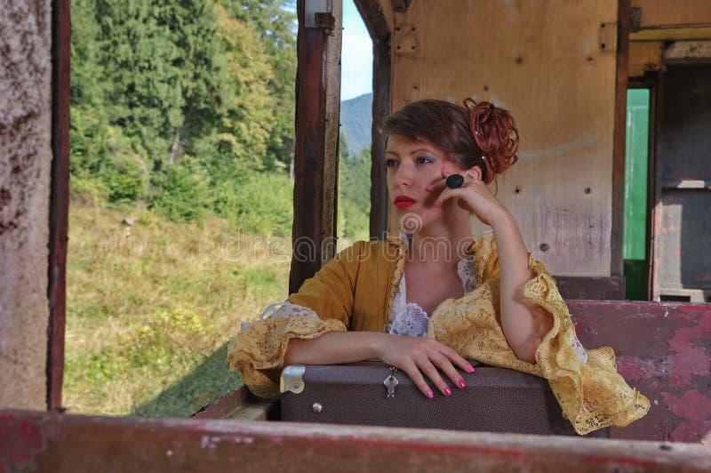 一列减速火箭的火车的妇女在窗口附近 免版税图库摄影