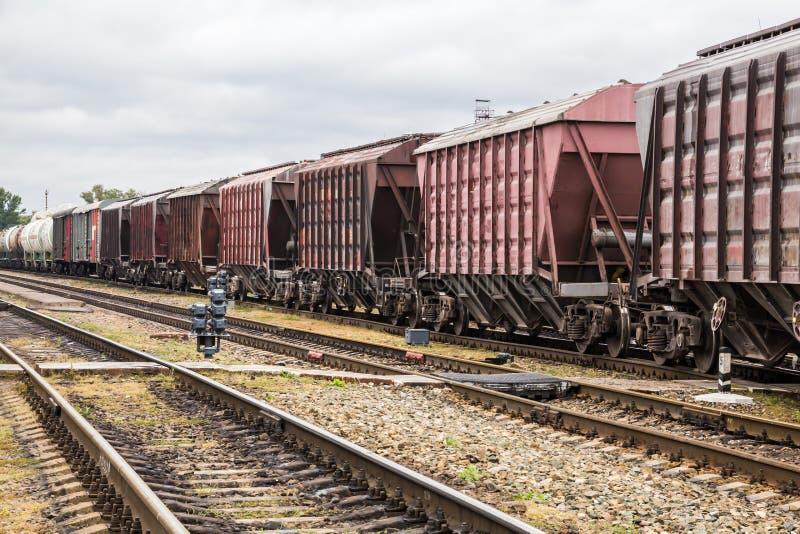一列货车的汽车在驻地的 用栏杆围铁路睡眠者 库存照片