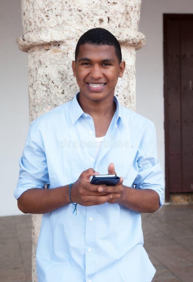 一则蓝色衬衣键入的消息的年轻人在电话 免版税库存照片