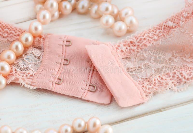 一副柔和的桃红色鞋带胸罩的钩子与珠色小珠的 免版税库存照片