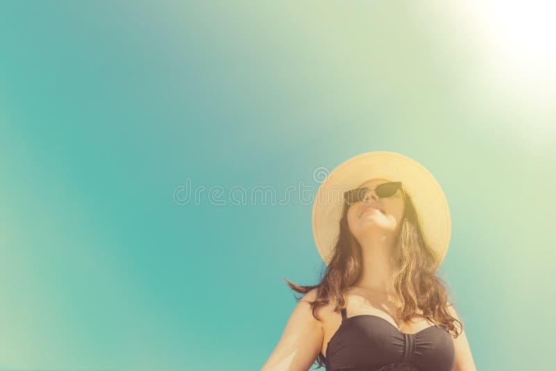 一副黑泳装的一年轻女人和帽子和太阳镜 在背景太阳和天空 ?? 度假胜地的概念和 库存照片
