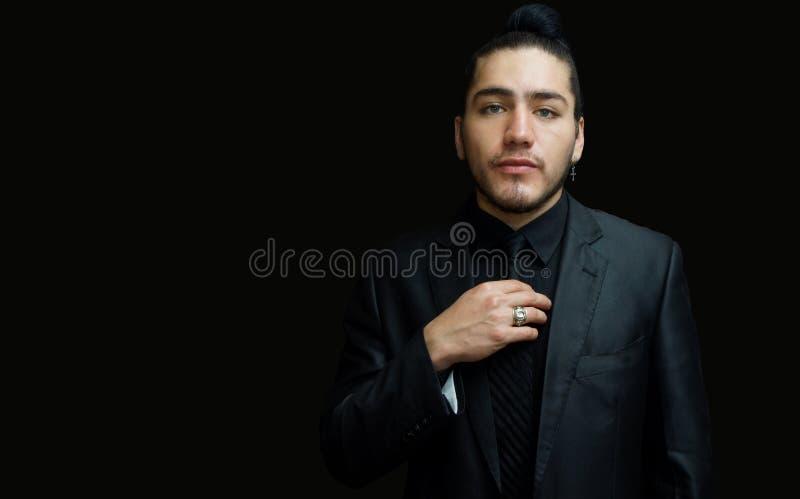 一副年轻拉丁人佩带的耳环的画象有黑衣服的,黑衬衣和半正式礼服在黑背景 库存图片