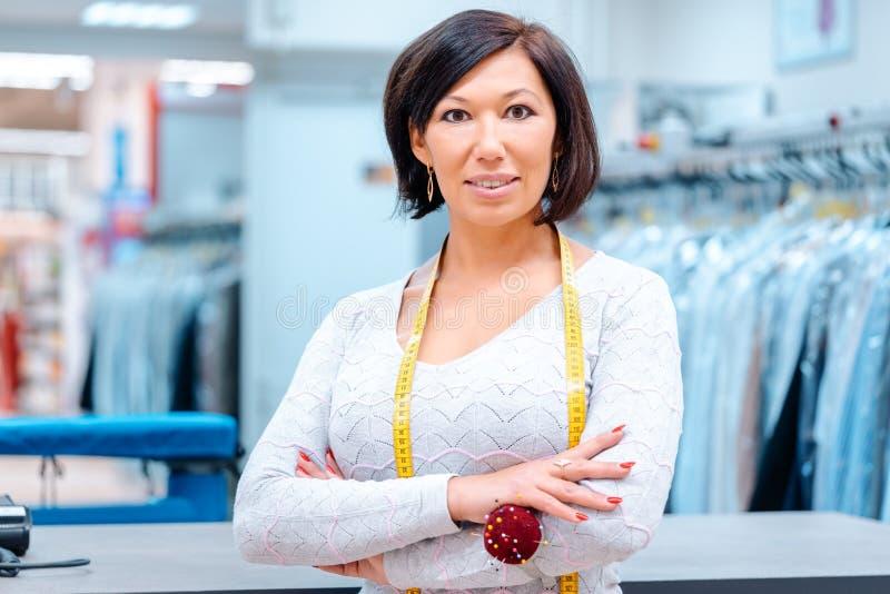 一化工纺织品擦净剂的所有者在她的商店前面的 库存照片