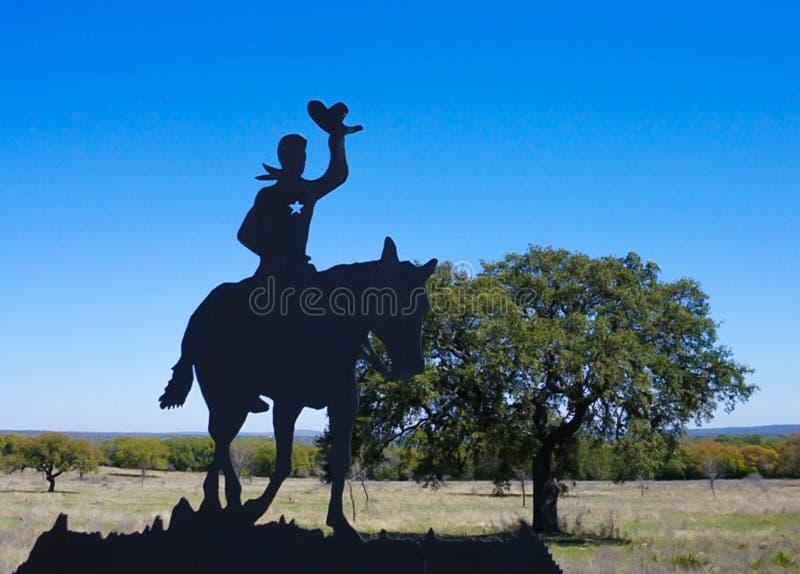 一匹牛仔和马在篱芭在一个农场在得克萨斯 免版税库存图片