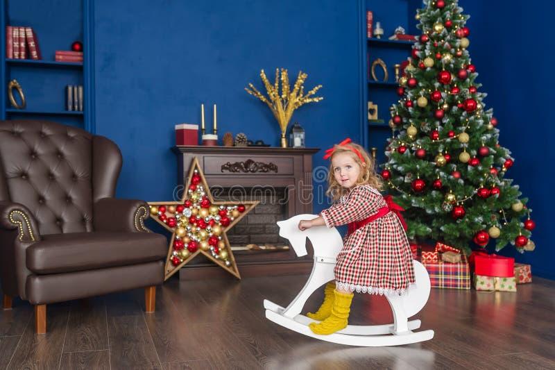 一匹玩具马的女孩在一棵圣诞树附近在蓝色本级教室 库存照片