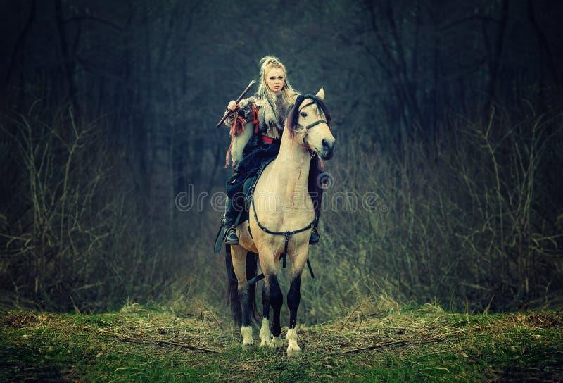 一匹马的战士妇女在森林 与轴的美丽的斯堪的纳维亚人北欧海盗骑乘马在手中 免版税库存照片