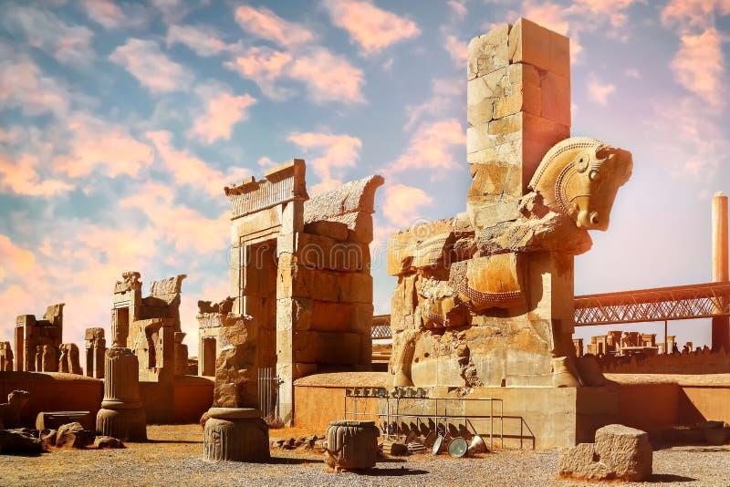 一匹马的石雕塑在反对蓝色和桃红色天空的波斯波利斯与云彩 日出 库存图片