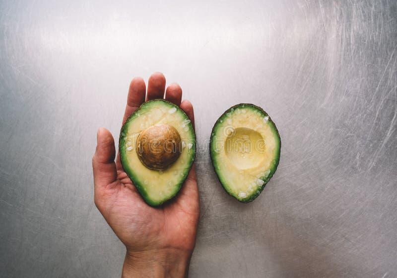 一半一个鲕梨在水平钢台式的视图的背景,在厨房的新鲜的健康食物早餐的一只手上 免版税图库摄影