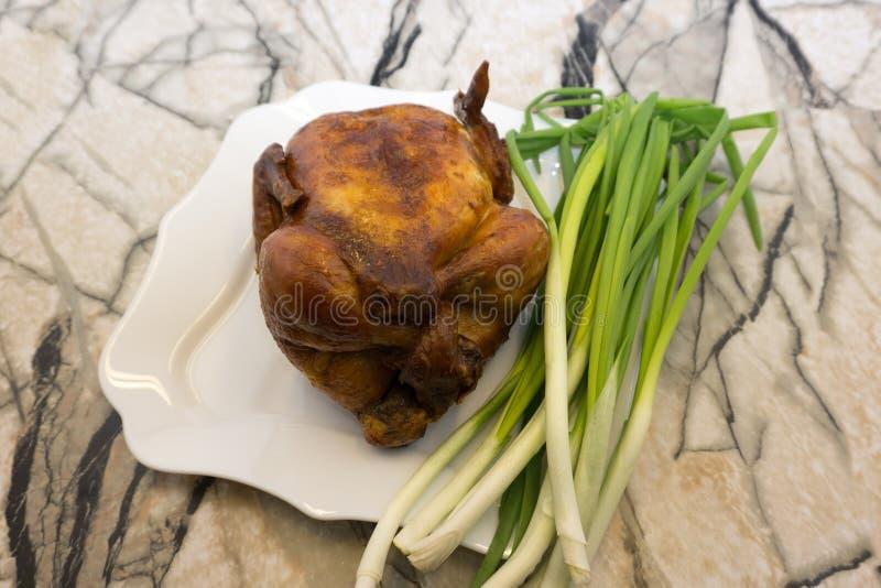 一半与金黄棕色外壳的开胃烤水多的鸡服务与石灰切片和荷兰芹在白色板材,在木选项 库存图片