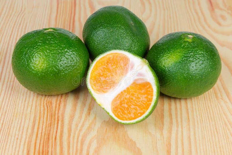 一半和几个整个成熟绿色蜜桔木表面上 免版税库存图片