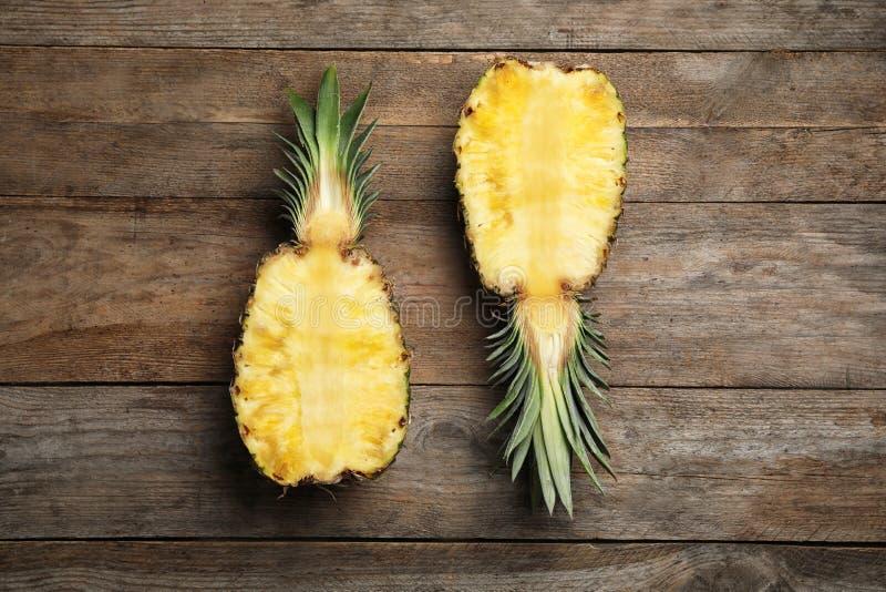 一半在木背景的新鲜的菠萝 库存图片