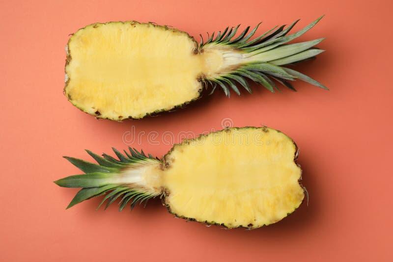 一半在橙色背景的新鲜的菠萝 免版税库存图片