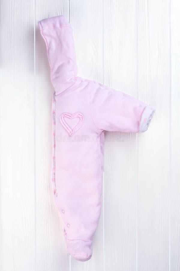 一半在白色木头的被折叠的女婴羊毛工作服 图库摄影