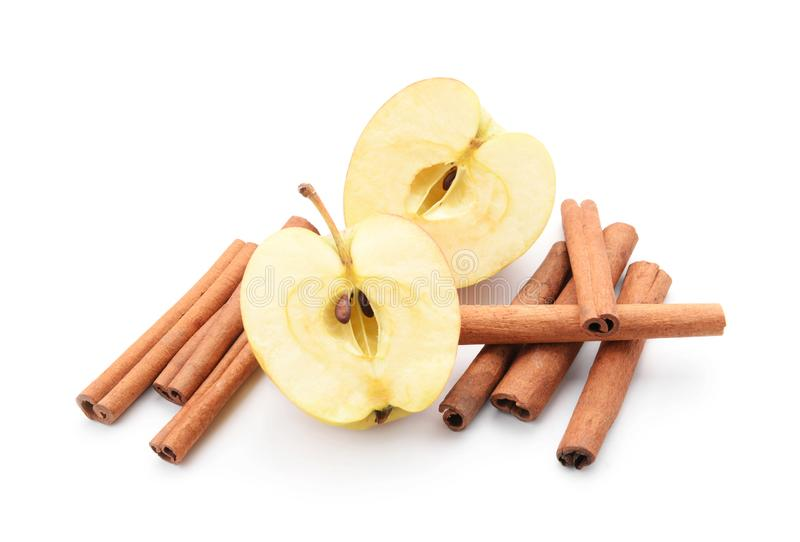 一半在白色背景的新鲜的苹果和肉桂条 库存图片