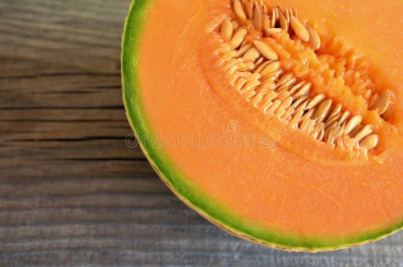 一半成熟有机甜瓜瓜香瓜, mushmelon,在老木桌上的rockmelon 免版税库存图片