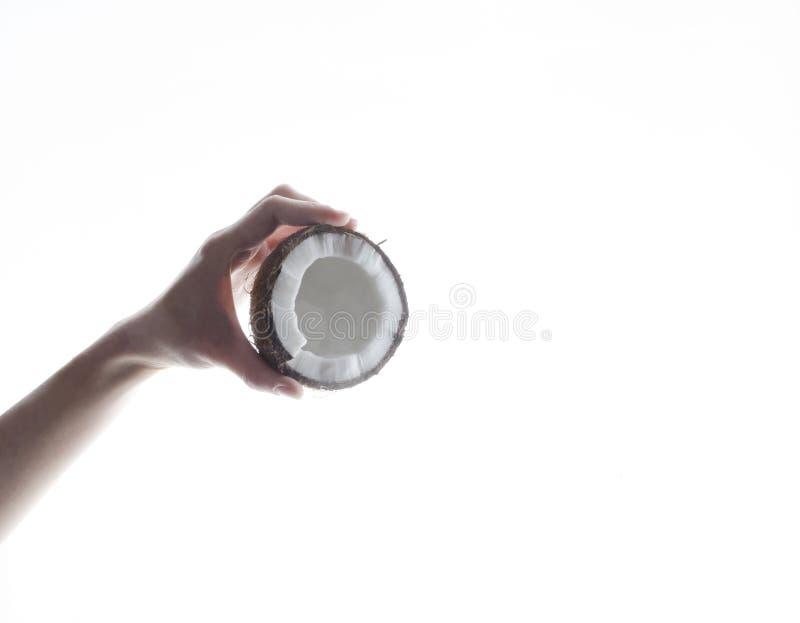 一半椰子在妇女手上 倾吐的椰奶的概念反对白色背景的 免版税库存图片