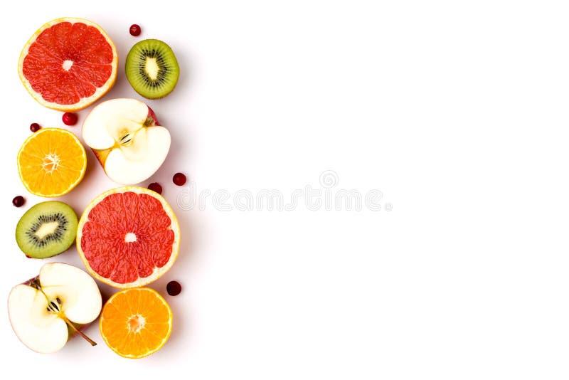 一半的背景成熟果子、猕猴桃、苹果、葡萄柚和普通话在白色 免版税库存图片