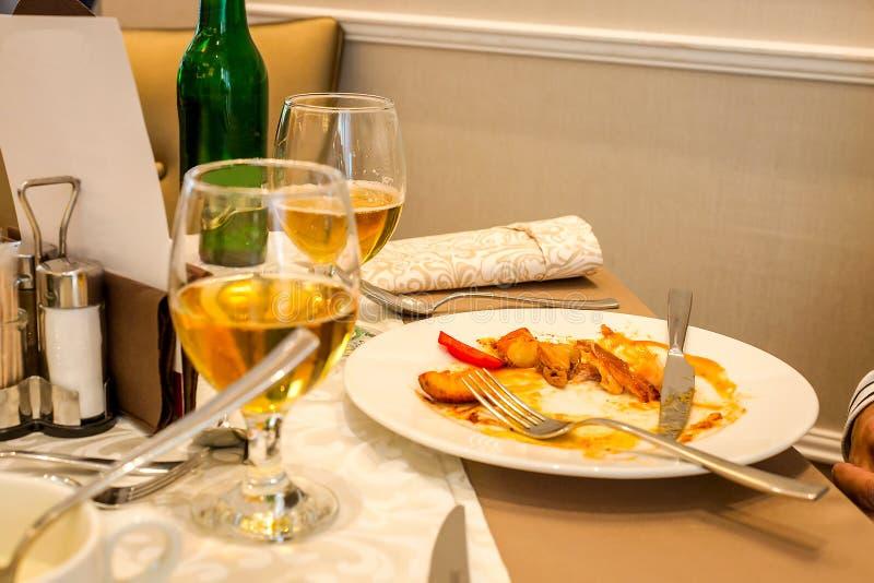 一半被吃的膳食和两杯在桌上的啤酒在餐馆 油煎的土豆和肉残余物在白色板材 免版税库存照片