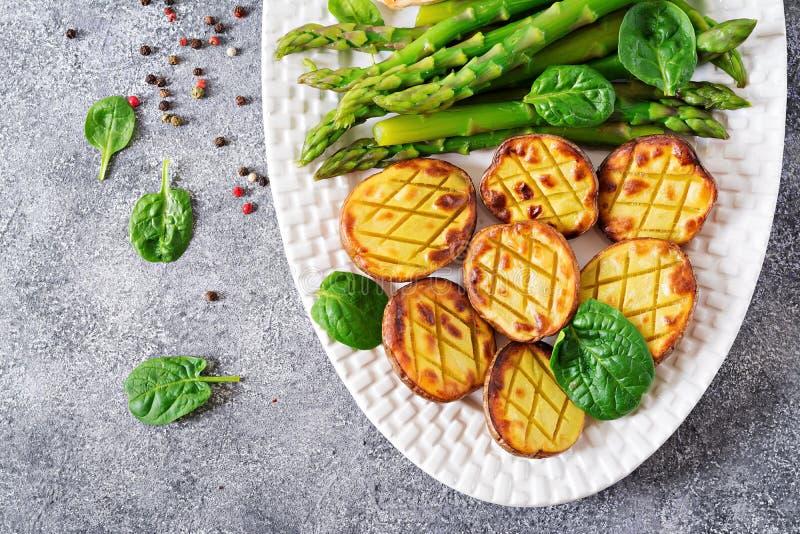 一半被烘烤的土豆和芦笋 饮食菜单 免版税库存图片