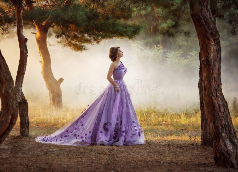 一华美紫色长礼服漫步的美丽的女孩室外 免版税库存图片