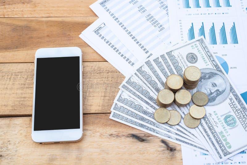 一叠硬币堆在美元钞票上,智能手机,木桌上的蓝色粉色图纸 商业、金融、市场 库存照片