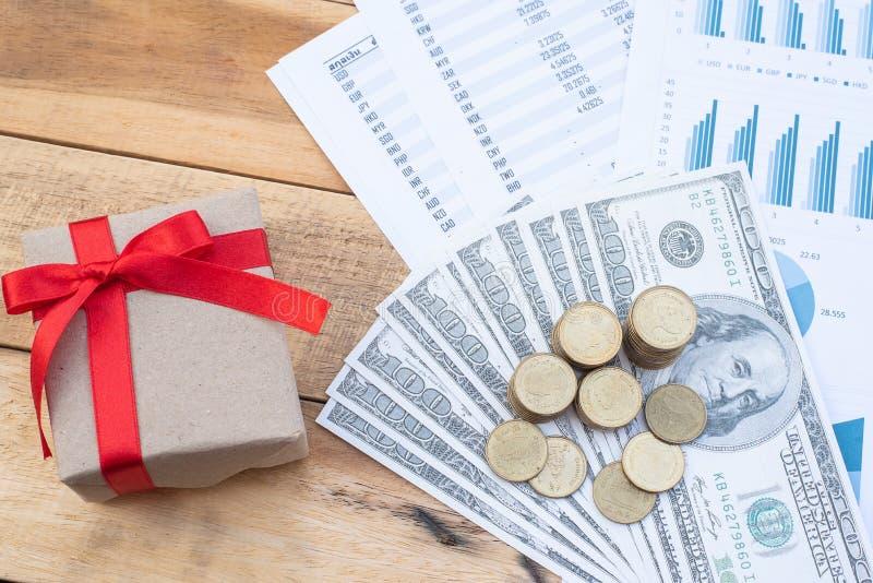 一叠纸币的平版纸、红丝带礼品盒、木桌上的蓝色柔和图纸 商业,金融, 库存图片