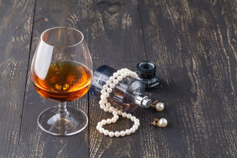 一口威士忌酒在典雅的典型的科涅克白兰地玻璃的白兰地酒在与女性首饰的黑背景 图库摄影