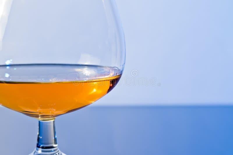 一口威士忌酒在典雅的典型的科涅克白兰地玻璃的白兰地酒在蓝色轻的背景 库存照片