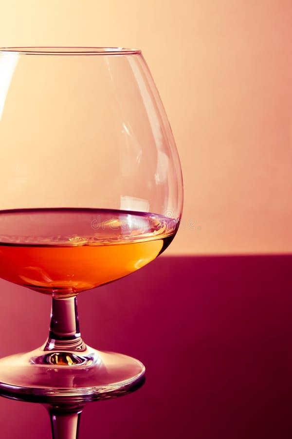 一口威士忌酒在典雅的典型的科涅克白兰地玻璃的白兰地酒在紫色上色了轻的迪斯科背景 免版税库存图片