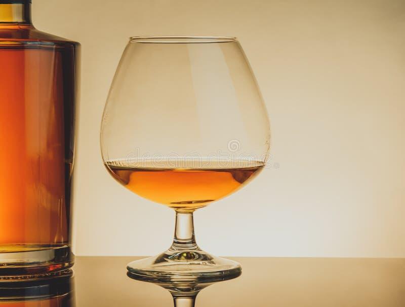 一口威士忌酒在典雅的典型的科涅克白兰地玻璃近的瓶的白兰地酒在桌,温暖的样式上 库存图片