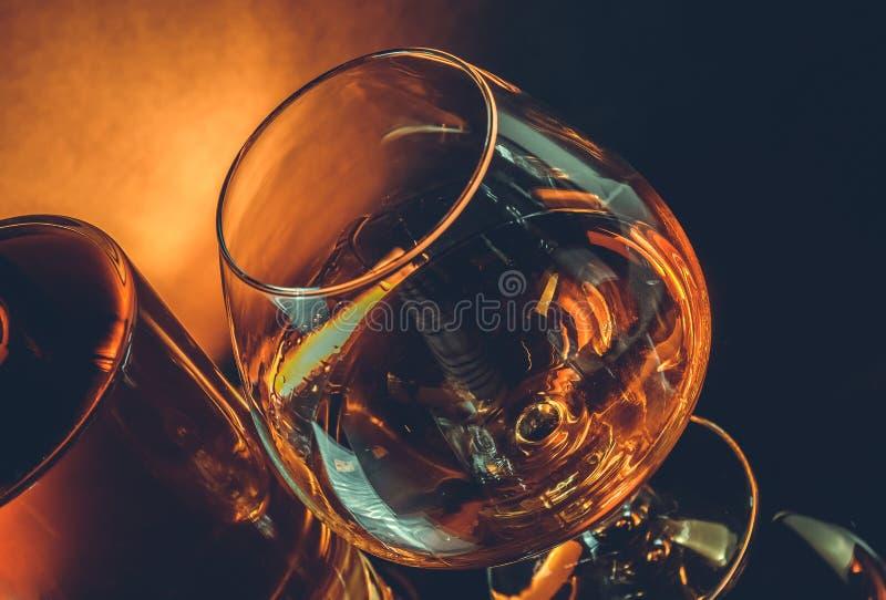 一口威士忌酒在典雅的典型的科涅克白兰地玻璃近的近的瓶的白兰地酒在黑桌,温暖的色彩样式上 免版税库存图片