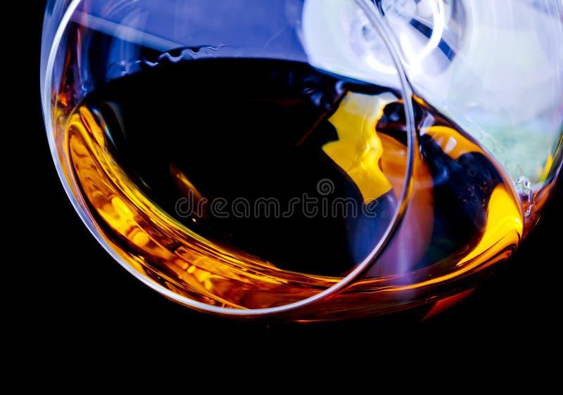 一口威士忌酒在典雅的玻璃的白兰地酒与文本的空间在轻的色彩蓝色迪斯科 免版税库存图片