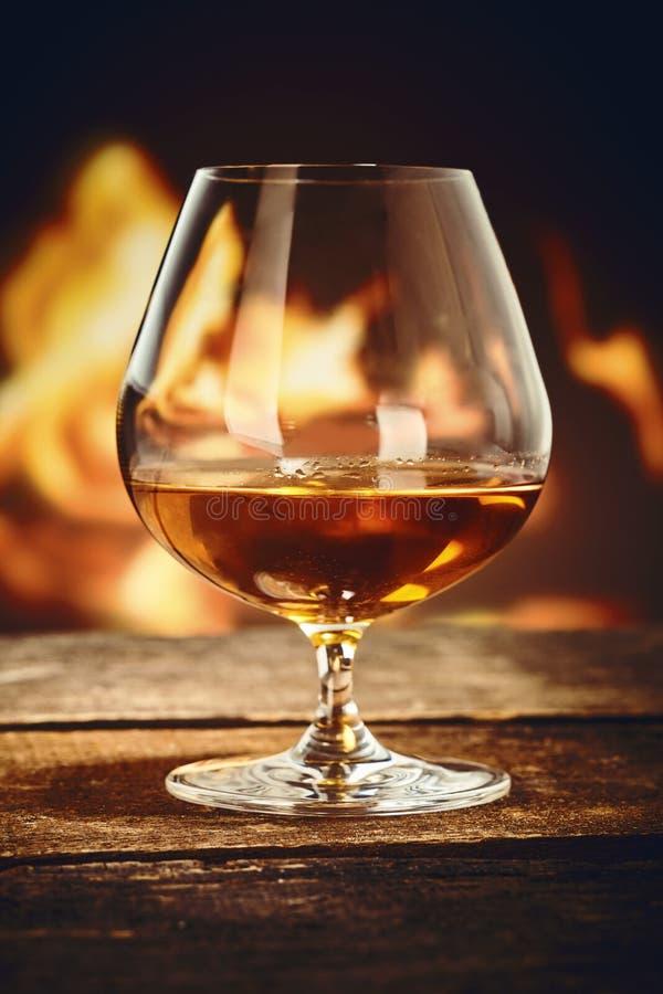 一口威士忌酒用在火前面的法国科涅克白兰地 库存照片