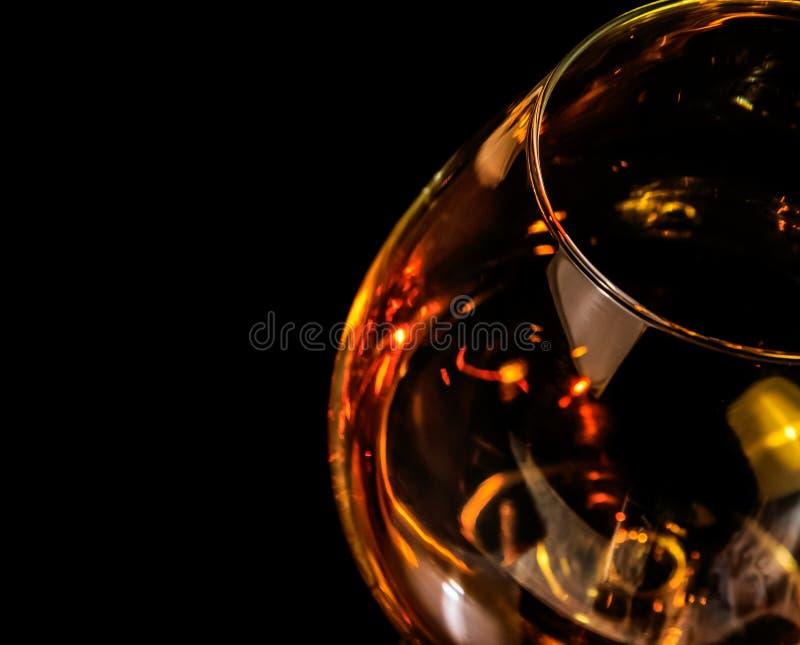 一口威士忌酒看法上面在典雅的典型的科涅克白兰地玻璃的白兰地酒在与红色反射的黑背景 库存图片